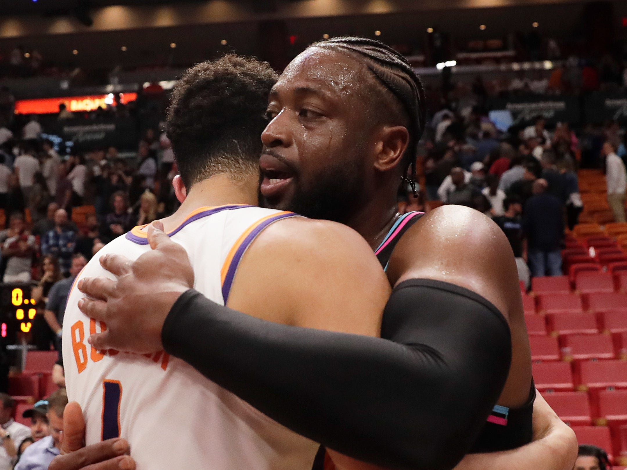 Miami Heat guard Dwyane Wade (3) and Phoenix Suns guard Devin Booker (1) hug before they exchange jerseys after an NBA basketball game on Monday, Feb. 25, 2019, in Miami, Fla. (AP Photo/Brynn Anderson)