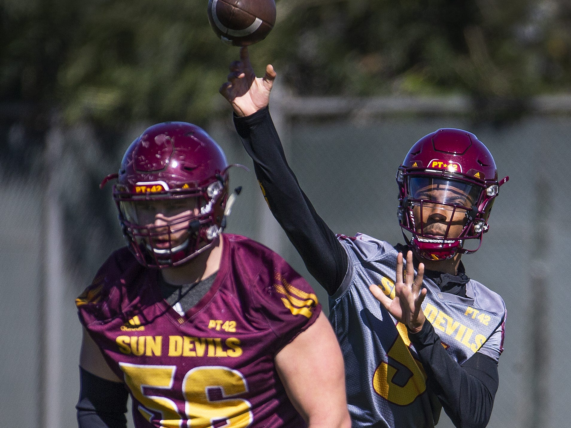 The Arizona State University football team practiced in Tempe, Tuesday, February 26, 2019.   Quarterback Jayden Daniels fires a pass as lineman Alex Losoya prepares to block.