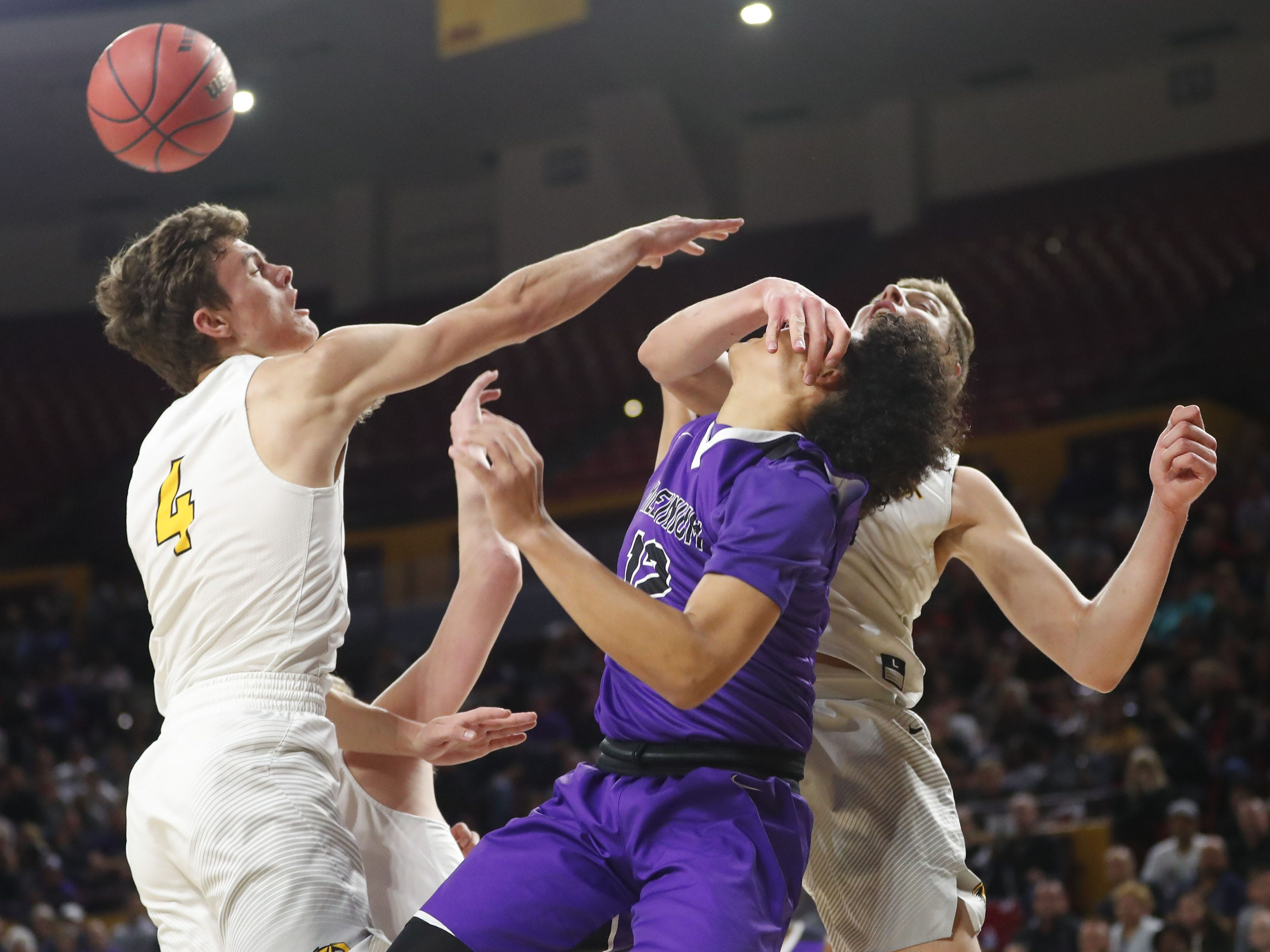 Gilbert's Carson Towt (33) fouls Millennium's Cameron Wilder (12) during the Boys State 5A Championship game in Tempe, Ariz. Feb. 25, 2019.