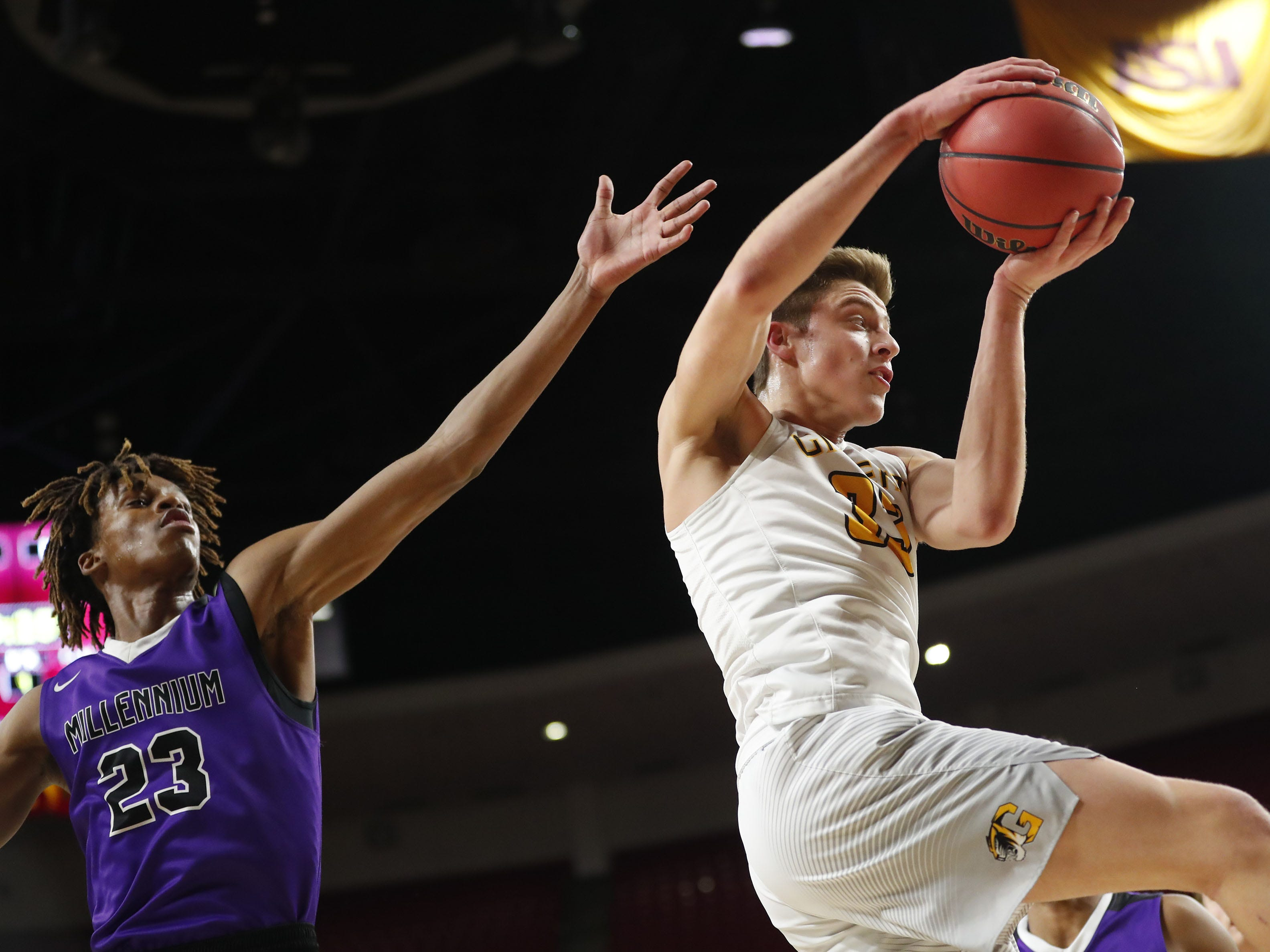 Gilbert's Carson Towt (33) grabs a rebound from Millennium's DaRon Holmes (23) during the Boys State 5A Championship game in Tempe, Ariz. Feb. 25, 2019.