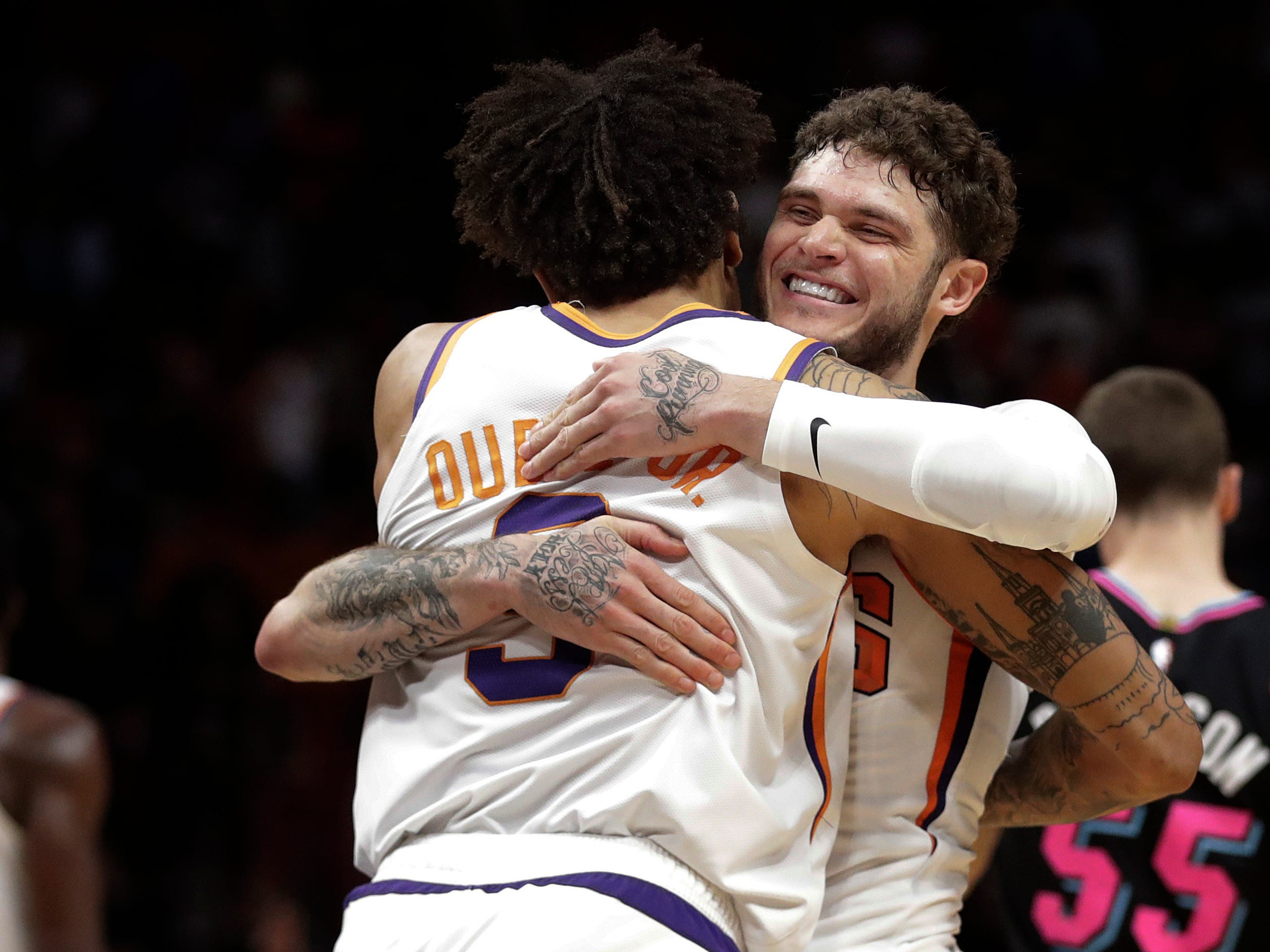 Phoenix Suns guard Tyler Johnson (16) hugs Phoenix Suns forward Kelly Oubre Jr. (3) after winning against the Miami Heat after an NBA basketball game Monday, Feb. 25, 2019, in Miami, Fla. Phoenix won, 124-121. (AP Photo/Brynn Anderson)