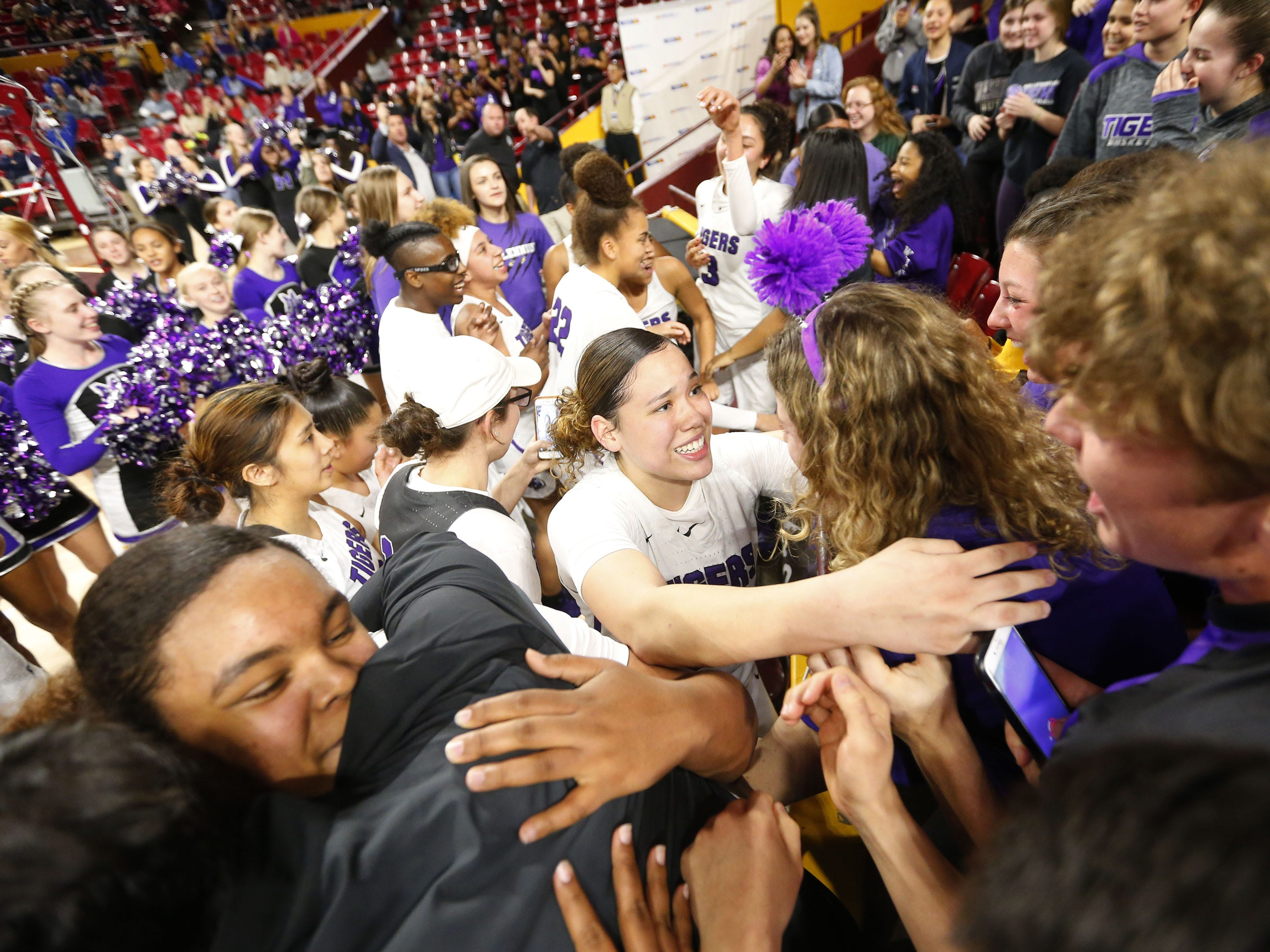 Millennium players celebrate with the student section after winning the Girls State 5A Championship game against Gilbert in Tempe, Ariz. Feb. 25, 2019.