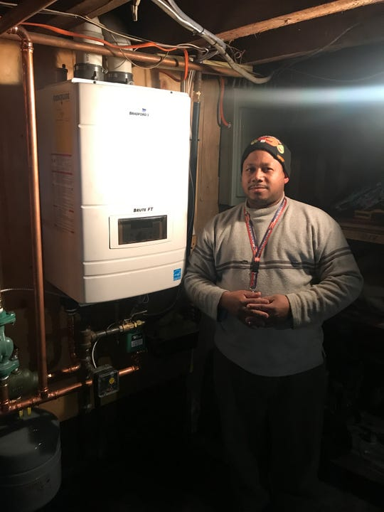 Eli Flores stands next to a new furnace in his basement, finally paid for by insurance.