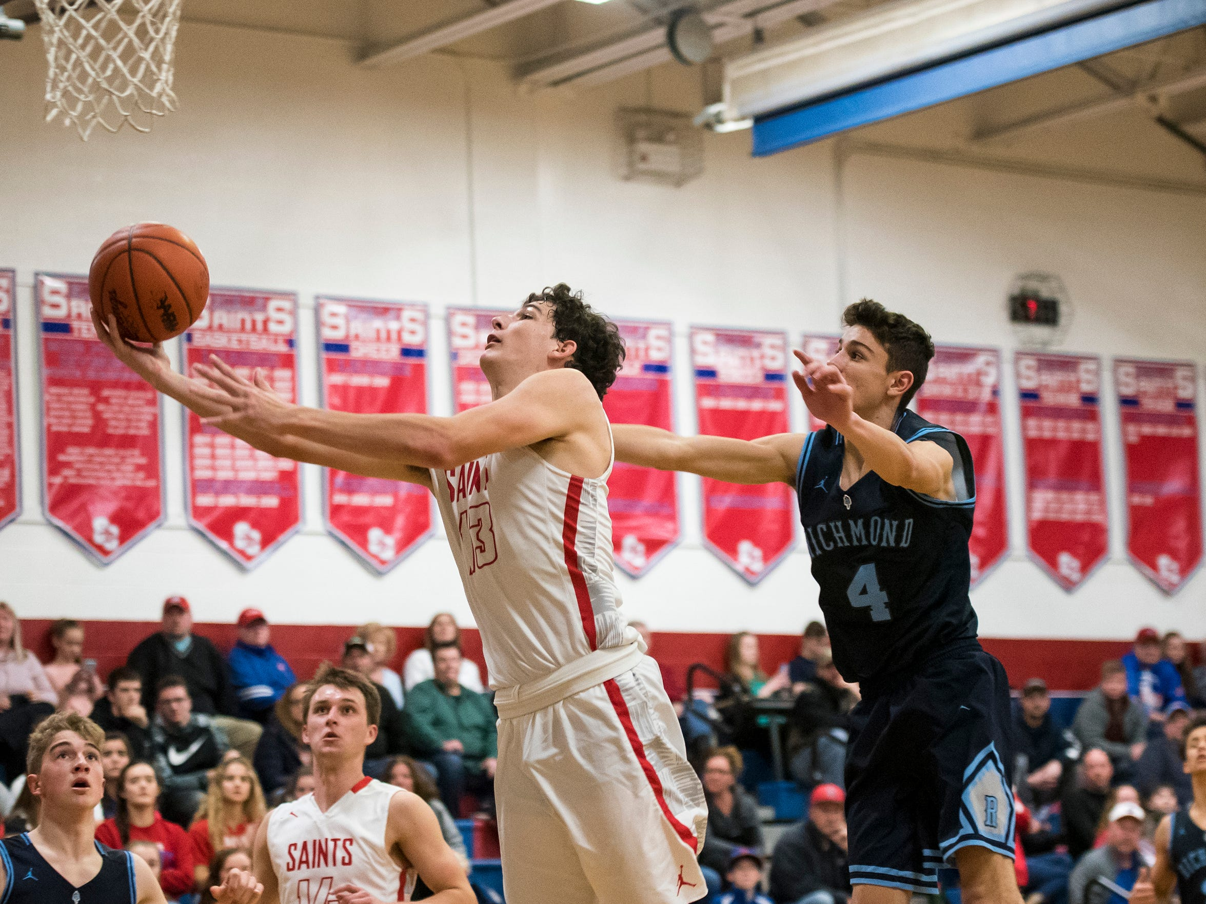 Richmond High School guard Brandon Schorman (4) reaches to block St. Clair's Ryan Zimmer during the first round of the MHSAA district basketball tournament Monday, Feb. 25, 2019 at St. Clair High School.
