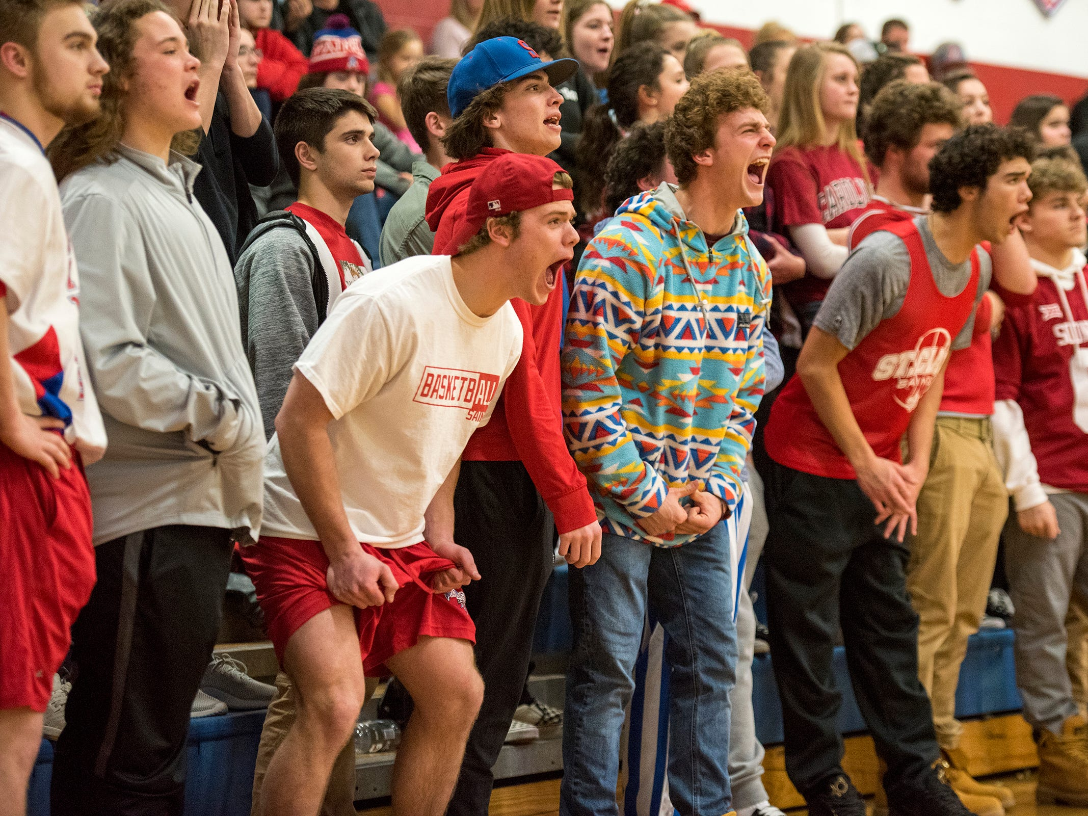 Fans try to cause a distraction while Richond High School forward Justin Schweiger shoots a free throw during the first round of the MHSAA district basketball tournament Monday, Feb. 25, 2019 at St. Clair High School.