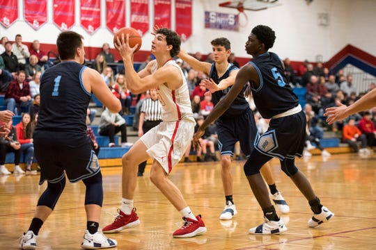 Players from Richmond High School defend against St. CLair's Ryan Zimmer (center) during the first round of the MHSAA district basketball tournament Monday, Feb. 25, 2019 at St. Clair High School.