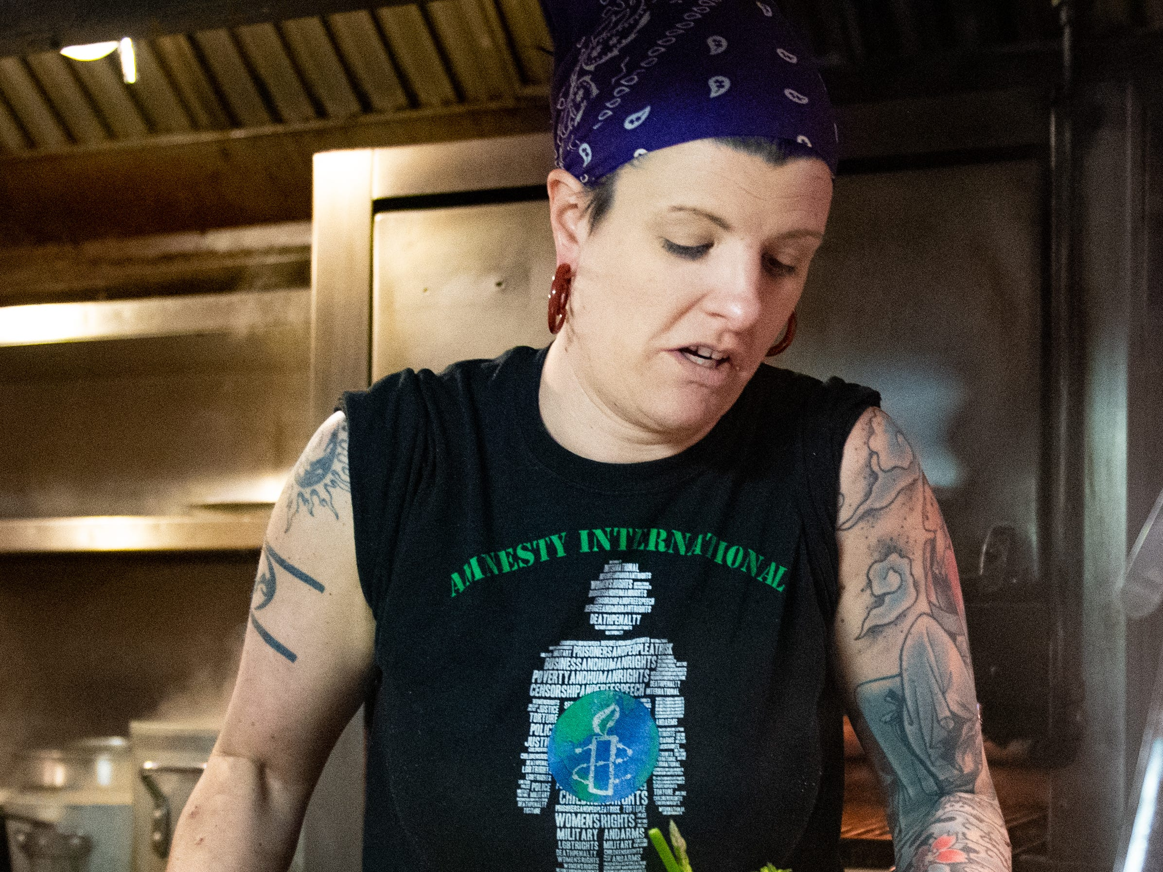 Executive Chef Corinna Killian carries a cutting board full of asparagus to another part of the kitchen at Bube's Brewery, February 22, 2019.