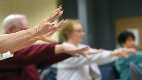 Seniors stretch their arms out and flex their wrists during a Matter of Balance class.