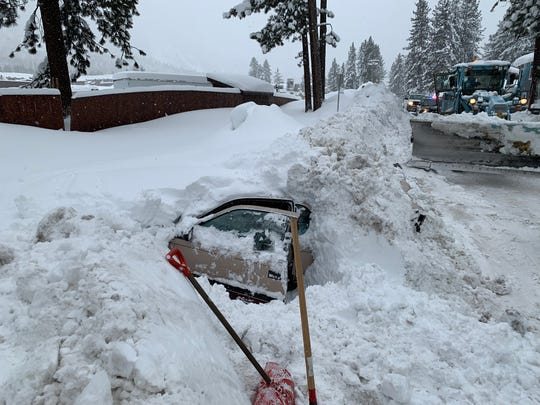 The pried open door of a vehicle fully buried in snow found after being struck by a snowplow in South Lake Tahoe. While digging out the vehicle to be towed, police found a 48-year-old woman still inside.