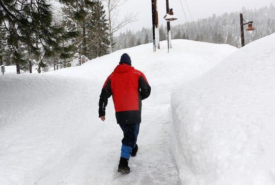 A man walks down a recently shoveled sidewalk in Tahoe City on Feb. 26, 2019.