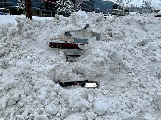 A rear view of a buried car struck by a snowplow in South Lake Tahoe. While digging the vehicle out to be plowed, police found a 48-year-old woman still inside.