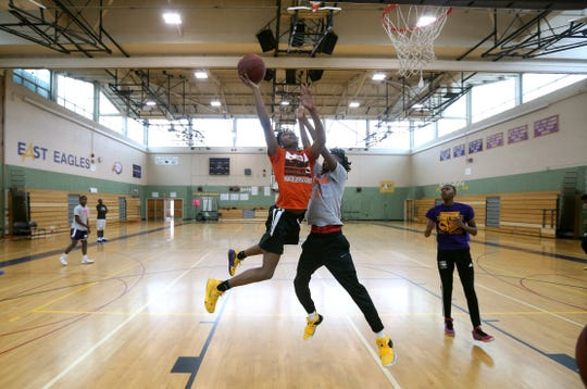 East's Maurice Coney, left, drives to the basket against teammate Kaori Barley during practice. Coney, a captain, is the nephew of East coach Darrell Barley and the cousin of Kaori Barley.
