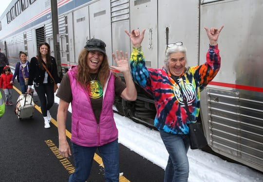 Patricia Bailey, center, and Annette Saba, right, celebrate as they disembark an Amtrak passenger train in Eugene, Ore. Tuesday, Feb. 26, 2019.  The train traveling from Seattle to Los Angeles with 183 passengers got stranded in the snowy mountains of Oregon for at least 36 hours, putting a strain on passengers as food, patience and even diapers ran short.