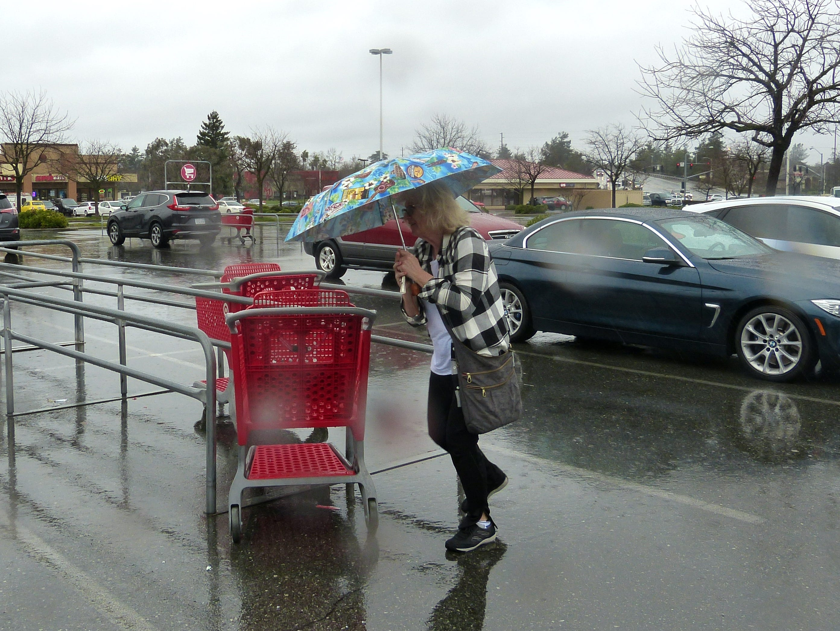 A shopper quickly tries to get out of the rain at the Target store in Redding on Tuesday.