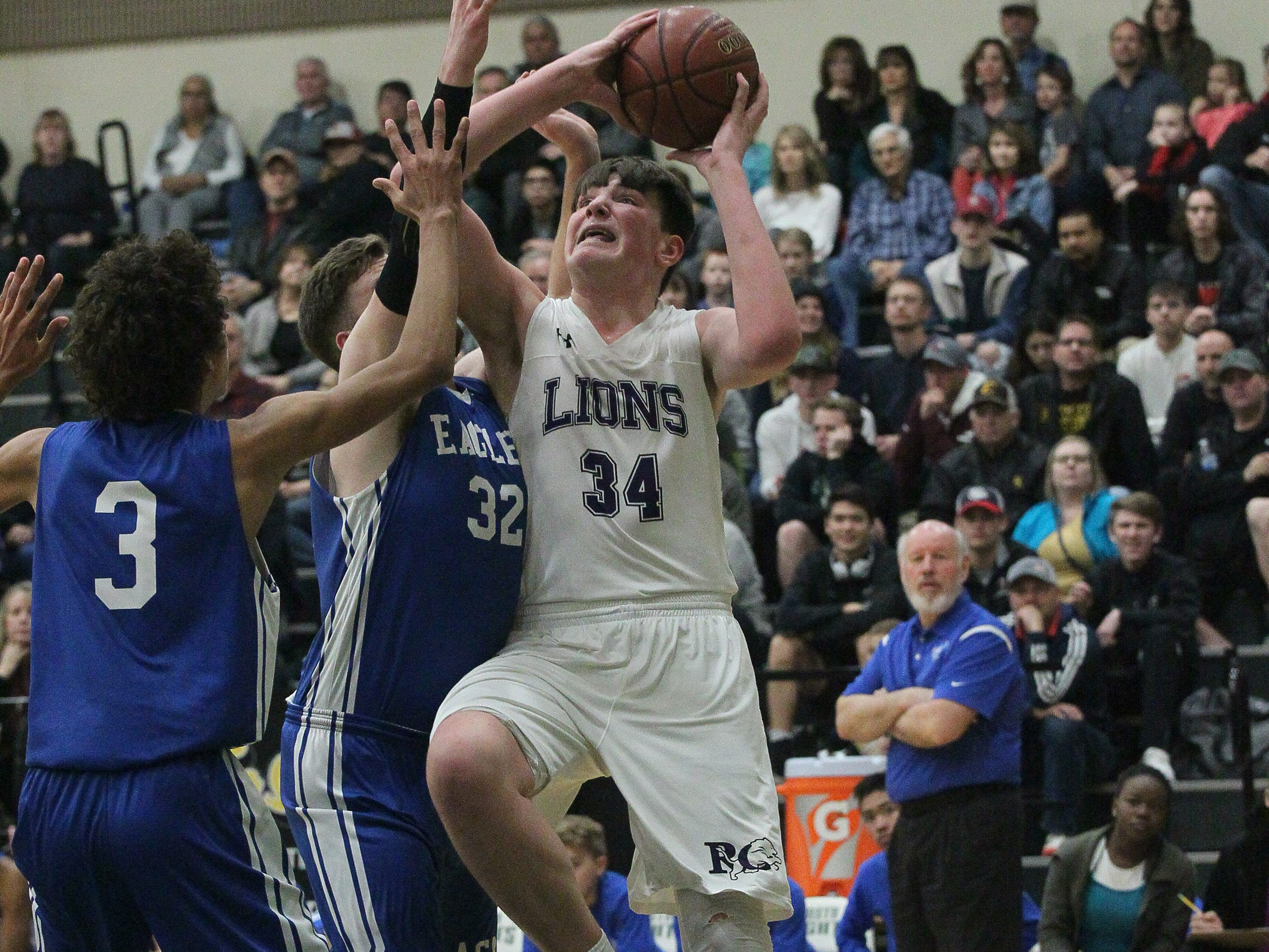Redding Christian's Andrew Nelson (34) goes up for the basket against American Christian's Matthew Edgar (32) and Elijah Nelson (3) during the Lions' 54-50 win in the Division VI Northern Section championship game at Shasta College on Saturday, Feb. 23.