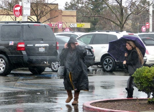 Shoppers head into the Redding Target store on Tuesday amid driving rain.