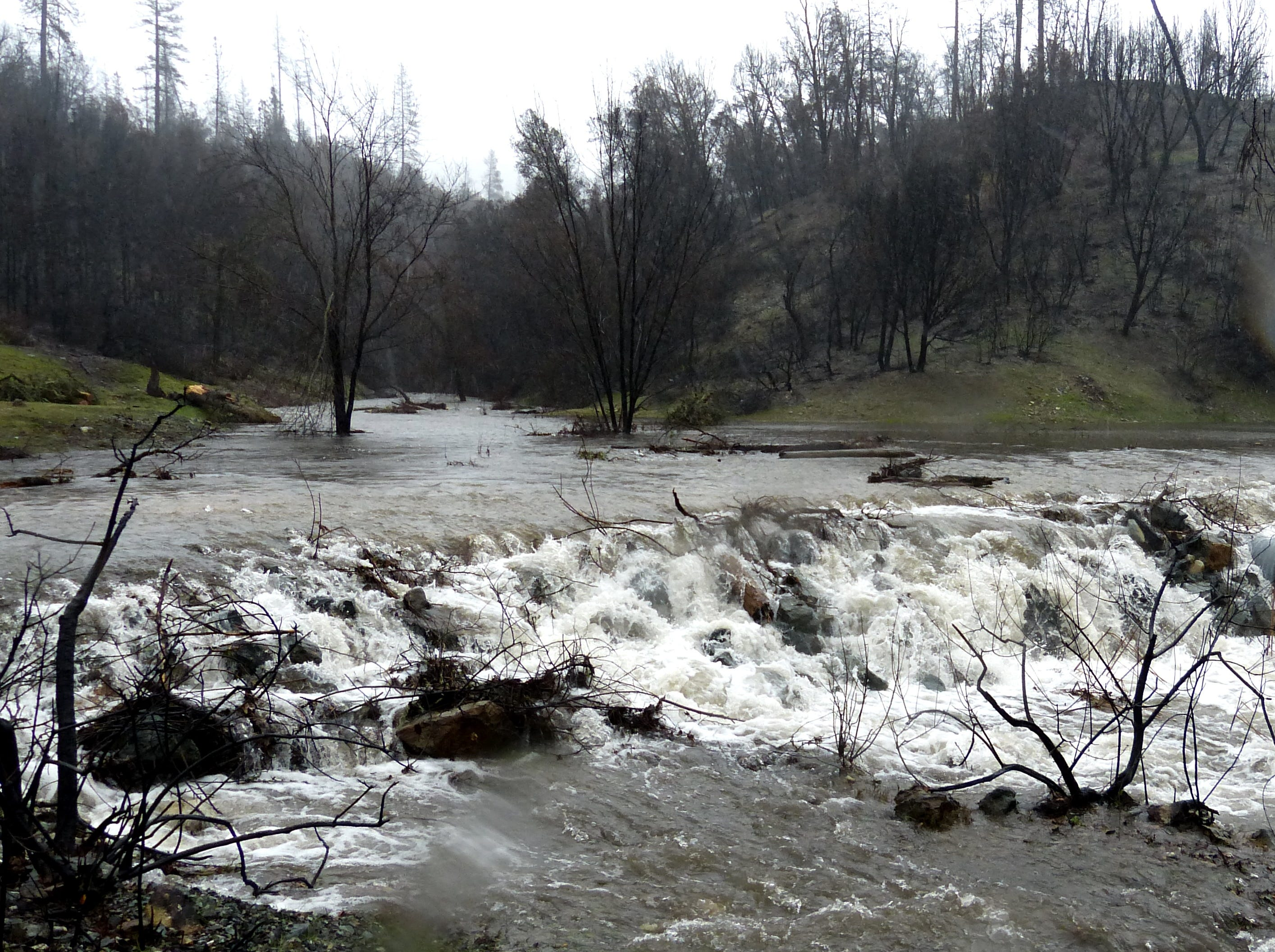 A rain-swollen creek rushes across Paige Bar Road at Whiskeytown National Recreation Area on Tuesday.