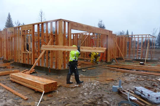 Andrew Scow and the rest of the crew with Crawford Building weren't daunted by the wind and rain Tuesday in Redding as they worked to rebuild a home in the Lake Redding Estates area that was destroyed by the Carr Fire last summer.