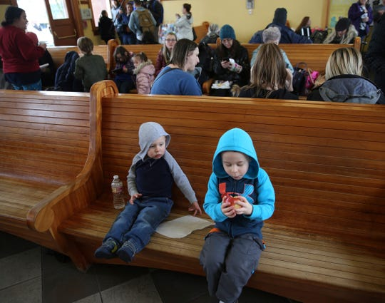 Ryder Albright, 2, left, and his brother Logan Albright, 5, get some food and water in the waiting area of the Eugene Amtrak Station with over a hundred other people after arriving, Tuesday, Feb. 26, 2019, Eugene, Ore., after being stranded with their parents overnight in the train in the mountains east of Eugene.