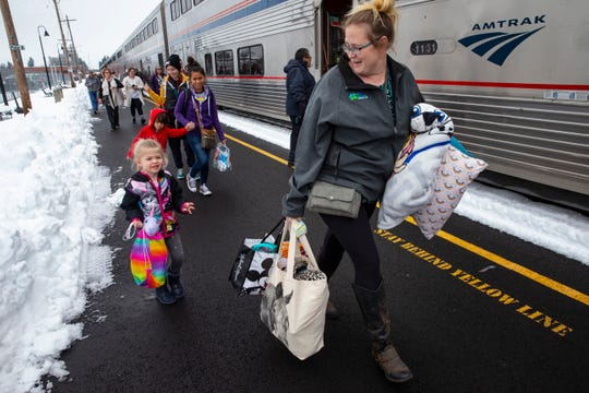 Jordyn Hooper, right, and her 4-year-old daughter Quinn Hooper, left, join other passengers as they disembark from an Amtrak train in Eugene, Ore, Tuesday, Feb. 26, 2019 after being stranded overnight in the mountains east of town.