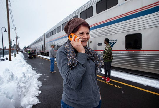 Tracy Rhodes, center, talks on the her phone while arriving in Eugene, Ore Tuesday, Feb. 26, 2019 after being stranded on the train overnight in the mountains east of Eugene, Ore.