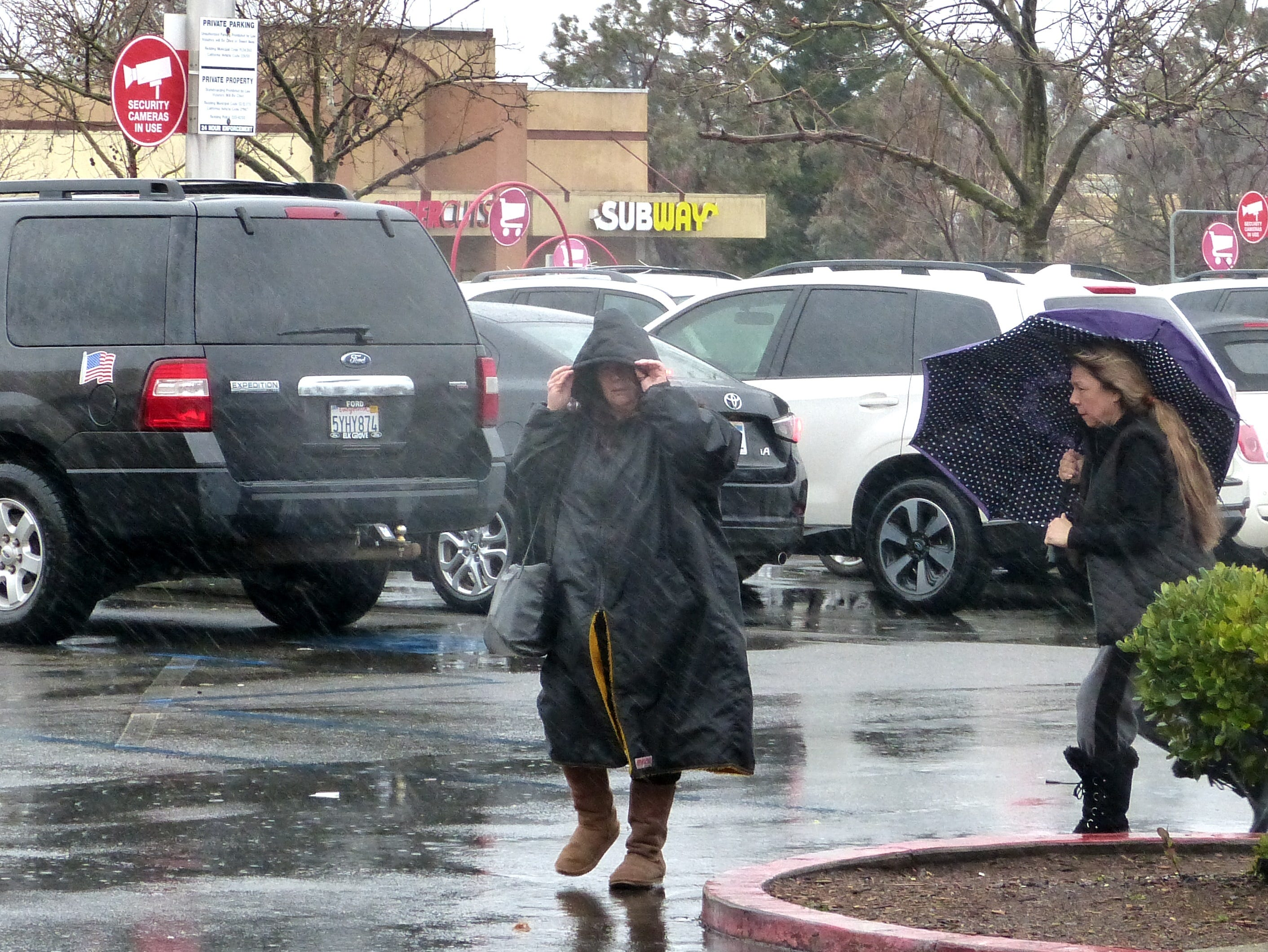 Shoppers hurry into the Redding Target store on Tuesday amid driving rain.