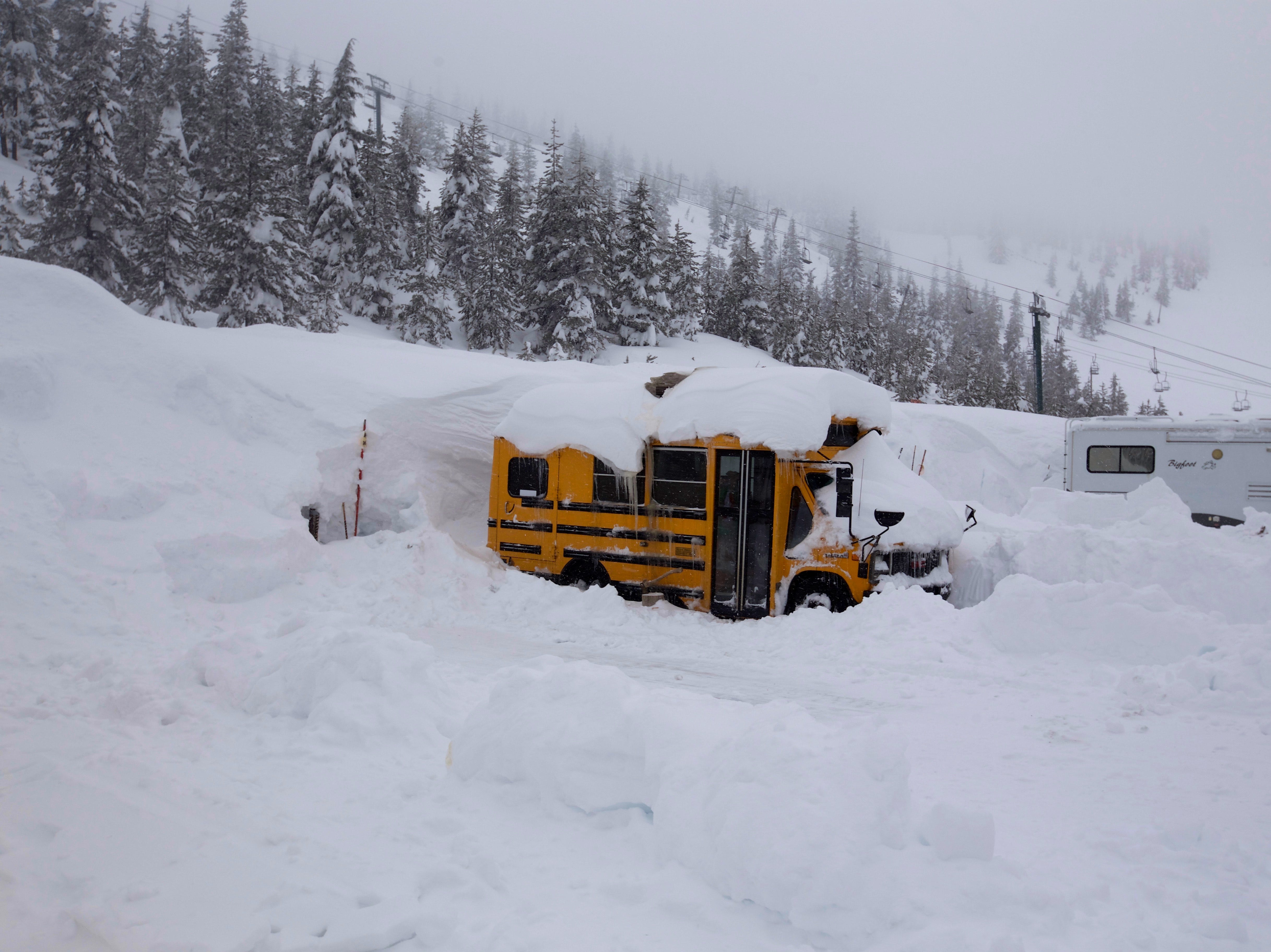 A small schoolbus covered in snow at Hoodoo Ski Area.