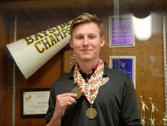 Crisfield High School track runner Kyle Noll shows off his state championship medals on Monday, Feb. 25, 2019.