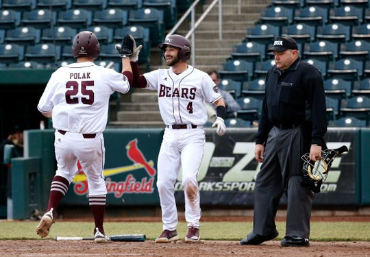 Missouri State's Joey Polak is high-fived by Logan Geha after scoring a run during a game against the Central Arkansas Bears at Hammons Field on Tuesday, Feb. 26, 2019.