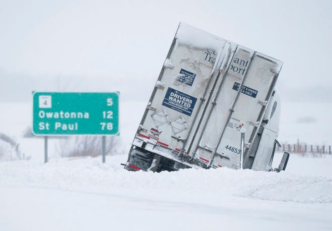 A tractor trailor is stuck in the snow on the side of Interstate 35 south of Owatonna on Monday, Feb. 25, 2019.