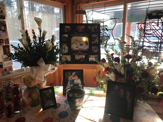 Keith Kitsembel-Rasmussen's ashes rest on a table surrounded by flowers, photos capturing his life and other momentos commeratating his memory.