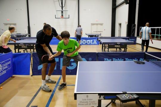 Tilden Corbett teaches Lucas Mauch, 14, a table tennis lesson at Northside Recreational Center Wednesday, Feb. 20, 2019.