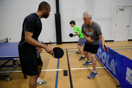 Tilden Corbett teaches a table tennis lesson to Steve Mauch and his son Lucas Mauch, 14, at Northside Recreational Center Wednesday, Feb. 20, 2019.