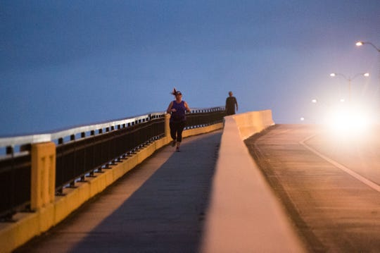 """Heather Coleman, of Stuart, runs across the Veterans Memorial Bridge in Palm City on Monday, Feb. 25, 2019, in preparation for the upcoming Marathon of the Treasure Coast. Coleman, who was a sergeant in the Army who spent19months in Iraq as an ammunition specialist, will be running her first marathon Sunday. """"For me, I feel like when I'm running...I just get into this zone where it's me and the road,"""" said Coleman, who was diagnosed with post-traumatic stress disorder after her service with the military. """"I just feel like it relieves everything."""""""