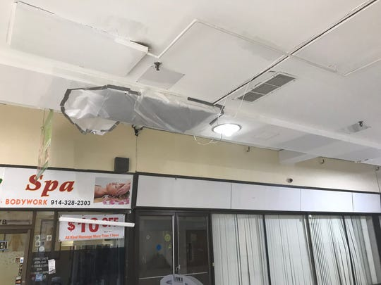 A section of the ceiling in the second-floor lobby of the White Plains Mall is covered by a tarp. The city took landlord WP Mall Realty to court, citing violations with regard to mold and a leaky roof. The case is still open.