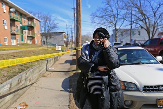 Nicole Owens, a resident at Robert Morris Apartment, speaks with friends on the phone outside her apartment where five of her neighbors were found dead Monday.