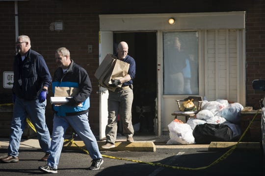 Investigators carry out items from the Robert Morris Apartments in Morrisville, Pa., Tuesday, Feb. 26, 2019. A woman and her teenage daughter are facing homicide charges in the deaths of five relatives, including three children.