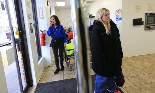 Pat O'Neill, a laundry attendant at Canal Laundry, a laundromat down the street from Robert Morris Apartments, looks out the window at the crime scene while customer Jamie Eatoa, waits for laundry to dry.