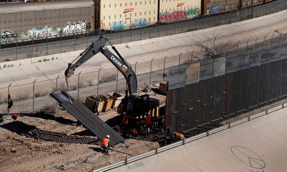 Workers place sections of metal wall as a new barrier is built along the Texas-Mexico border near downtown El Paso, Texas, on Jan. 22, 2019.