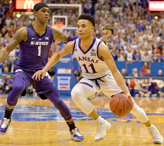 Kansas guard Devon Dotson dribbles the ball while defended by Kansas State guard Shaun Neal-Williams.
