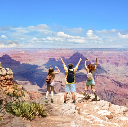 People with hands up jumping  and having fun on the top of the mountain. Family vacation in  beautiful  mountains looking at coastal landscape..Grand Canyon National Park, Arizona, USA