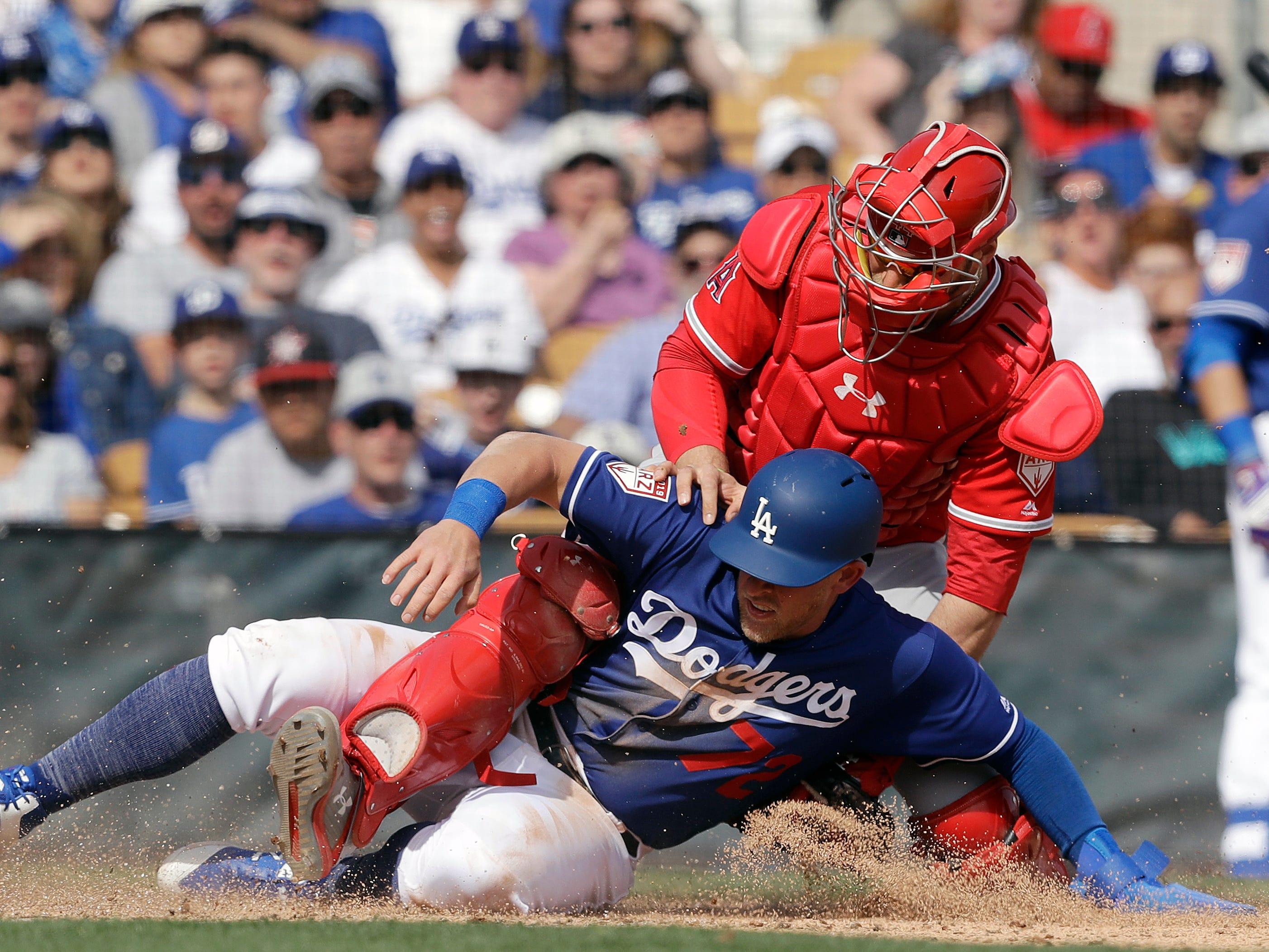 Feb. 24: Dodgers' Matt Beaty, bottom, scores on an error by Angels catcher Kevan Smith.