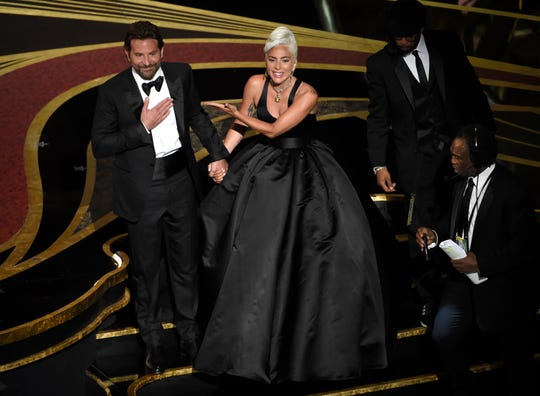 """Bradley Cooper, left, and Lady Gaga bask in the audience applause after their performance of """"Shallow"""" from the Oscars."""