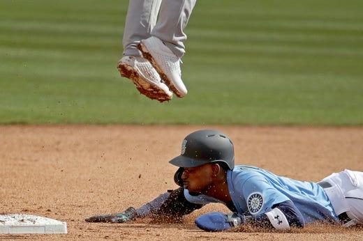 Feb 22: Mariners' Dee Gordon slides under Athletics second baseman Franklin Barreto to steal second base.
