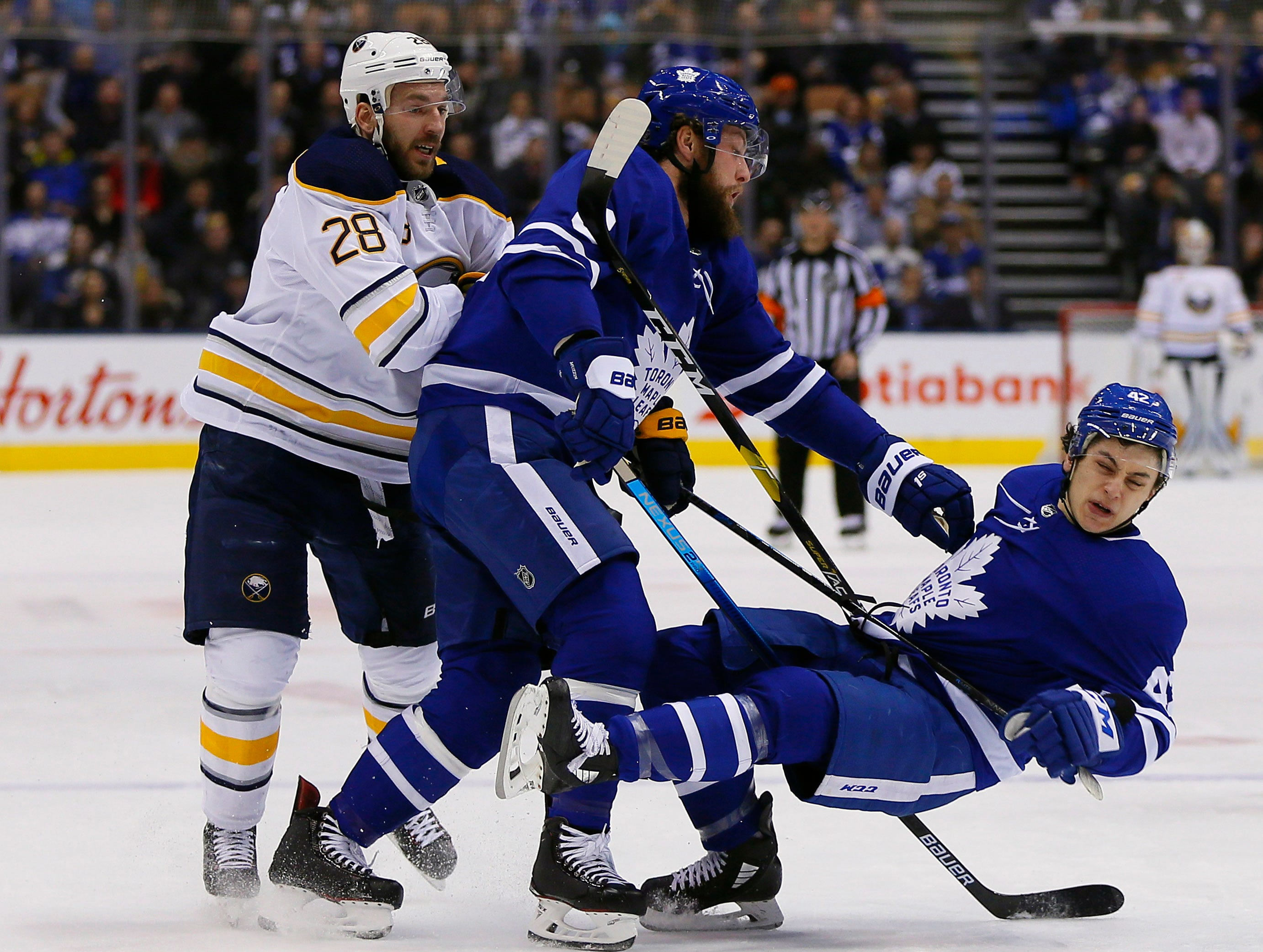 Feb. 25: Toronto Maple Leafs defenseman Jake Muzzin (8) and forward Trevor Moore (42) collide as Buffalo Sabres forward Zemgus Girgensons (28) looks on during the first period at Scotiabank Arena.