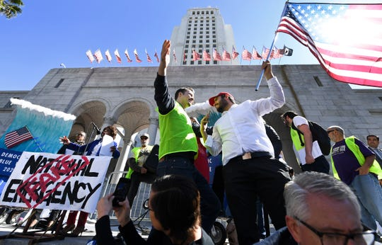 A Trump supporter holding an American flag confronts a security guard during a Los Angeles protest against President Trump's declaration of emergency to build a border wall.