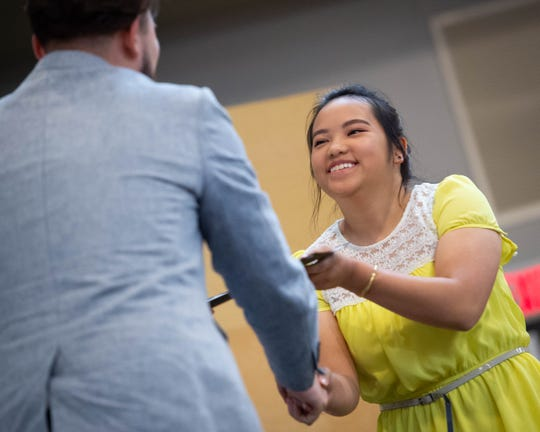 Kao Lee Thao accepts a certificate from Titan Advantage Program Daniel Salazar, a TAP peer mentor, at a recognition ceremony in 2016.