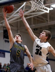 Ashwaubenon's Matt Imig goes for a layup while being covered by Menasha's Jordan Nowak during a 2019 game.