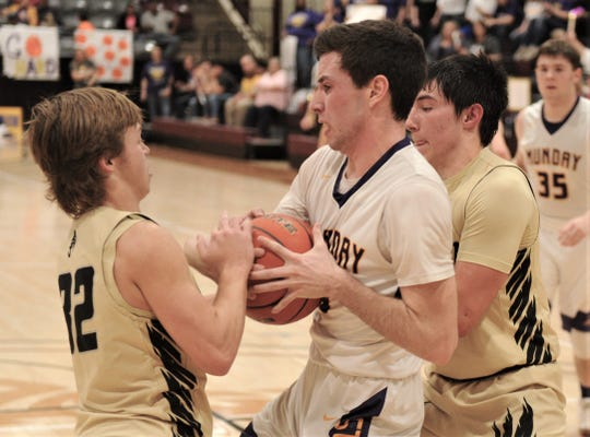 Jayton's Tye Scogin, left, and Pecos Smith, right, defend against Munday's Brendan Kuehler. Jayton beat the Moguls 53-49 in the Region II-1A quarterfinal playoff game Tuesday, Feb. 26, 2019, at McMurry's Kimbrell Arena.