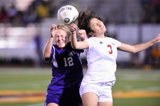 Wylie's Kaitlyn Via (12) and Cooper's Anessa Garcia (3) go up for a header at Bulldog Stadium on Tuesday, Feb. 26, 2019. The Lady Cougars won 1-0.